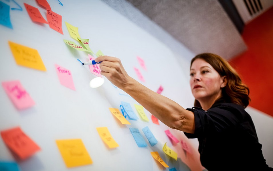 Elizabeth Hinckley writes on a white board covered in Post-its