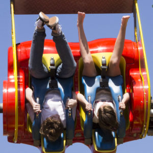 Two people hang upside down in a roller coaster
